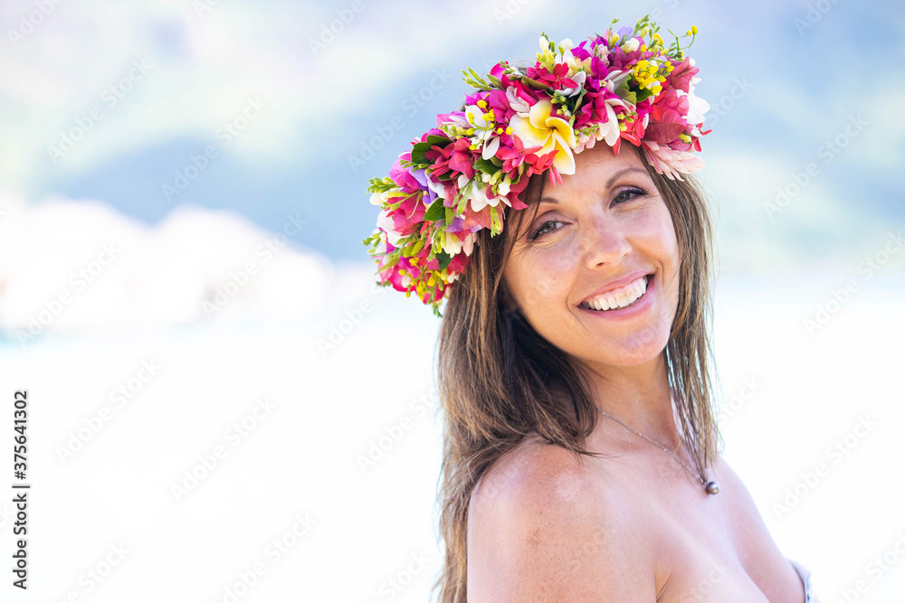 Fototapeta Beautiful woman wearing colorful flower crown while on a tropical island vacation in Bora Bora near Tahiti in French Polynesia