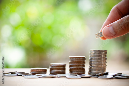 Fotografia Human hand putting coins of growing in the future with bokeh background