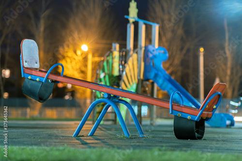 Seesaw swing in preschool yard with soft rubber flooring at night Fotobehang