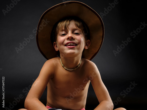 Fototapety, obrazy: Close up of young smiling cowboy against a black background.