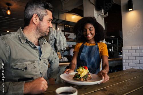 Obraz na plátně African America waitress serves handsome man food at funky restaurant