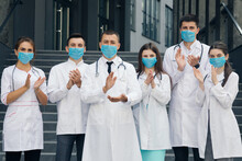 Medical Staff From The Hospital Who Are Fighting Coronavirus Applaud Back The People And Police Officers For Their Support. Group Of Doctors With Face Masks. Corona Virus And Healthcare Concept