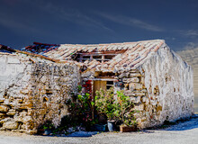 A Dilapidated House In The Eve...