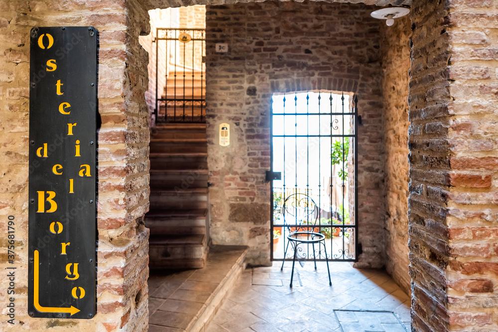 Montepulciano, Italy - August 28, 2018: Via Ricci street in small town village in Tuscany during summer with restaurant and hotel entrance called Osteria del Borgo
