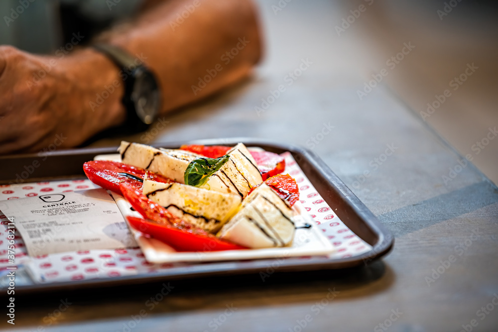 Florence, Italy - August 30, 2018: Firenze Centrale Mercato central market with closeup of dining table with dish of mozzarella, tomatoes, and balsamic vinegar with basil leaves
