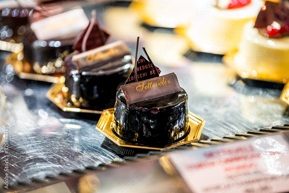 Florence, Italy - August 30, 2018: Firenze central market with Beduschi sign closeup of chocolate dessert yellow custard pastries on tray display in bakery shop store