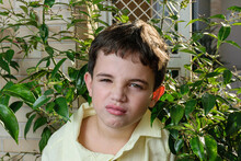Close-up Of A 7-year-old Brazilian Child, Finding It Bad Because It Is In The Middle Of The Foliage.