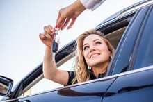 Beautiful Woman Gets The Key From The Car While Sitting Behind The Wheel.