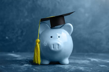 Piggy Bank With Graduation Hat On Table. Tuition Fees Concept