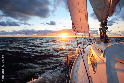 Foto Yacht sailing in an open sea at sunset