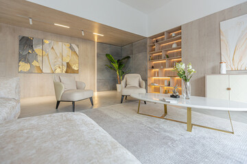 modern interior design of the living area in the studio apartment in warm soft colors. decorative built-in lighting and soft beige furniture