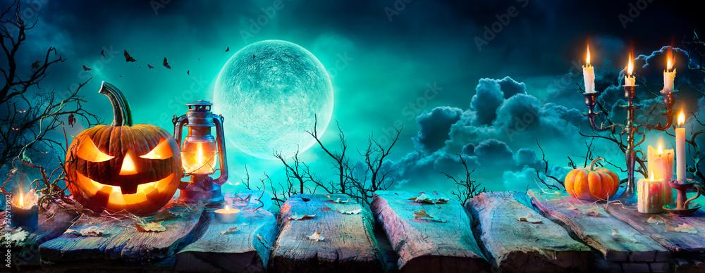 Fototapeta Jack O' Lantern On Table In Spooky Night - Halloween With Full Moon