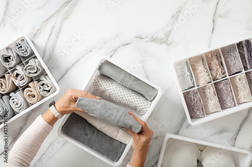 Woman hands neatly folding underwears and sorting in drawer organizers on white marble background Fototapet
