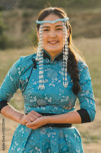 Mongolian woman wears national costume in a desert at sunset. Canvas-taulu