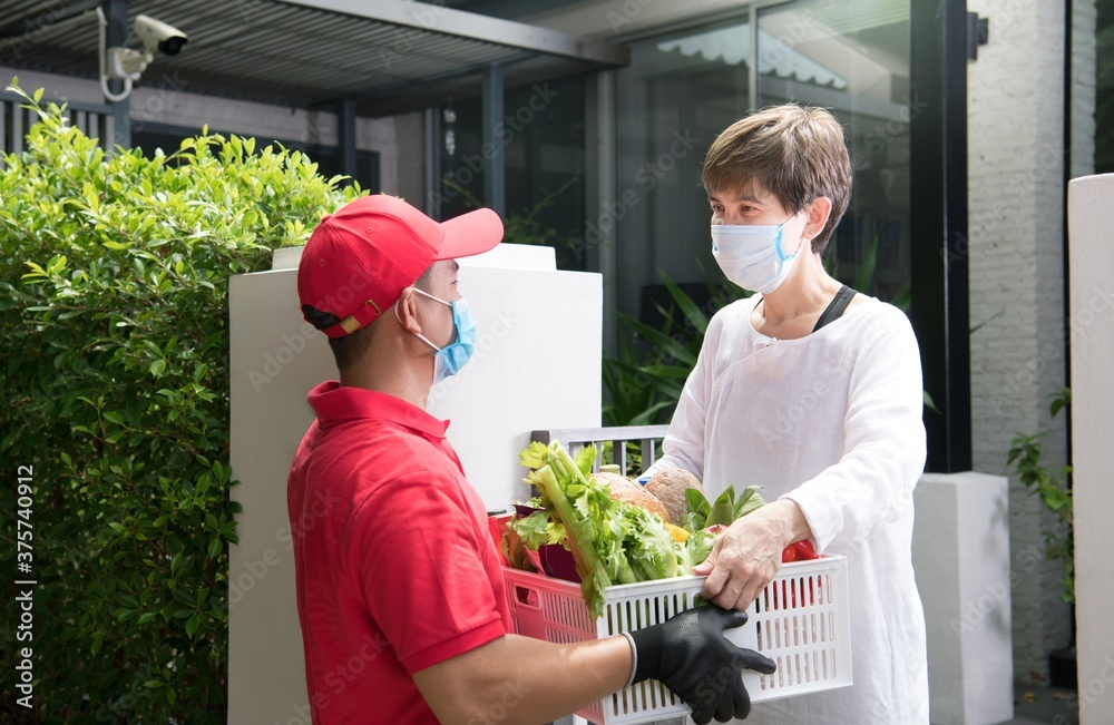 Fototapeta Asian delivery man wearing face mask and gloves in red uniform delivering  groceries box of food, fruit, vegetable and drink to recipient during COVID-19 outbreak
