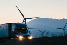 Tractor Trailer Transporting Cargo On Highway During Evening With Windmills On Roadside