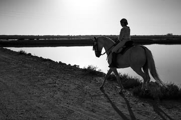 Chica con caballo yegua tordo torda playa natural camino trote doma playa salina camino naturaleza sanlucar rocio virgen campo ecuestre