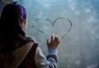Young girl drawing a smiling heart on a window