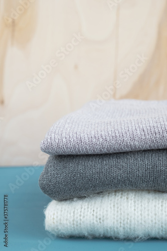 Stack of knitted sweaters on blue wooden table Slika na platnu