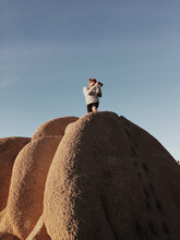 Man Taking A Picture On Top Of A Huge Rock