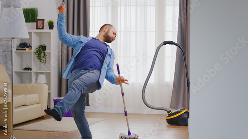 Fotografia Excited young man dancing while cleaning his apartment.