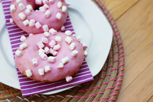 Pink Glazed Donuts With Little Marshmallow On A Plate On Wooden Background