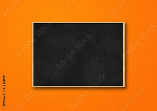 Traditional black board isolated on orange background Fotobehang