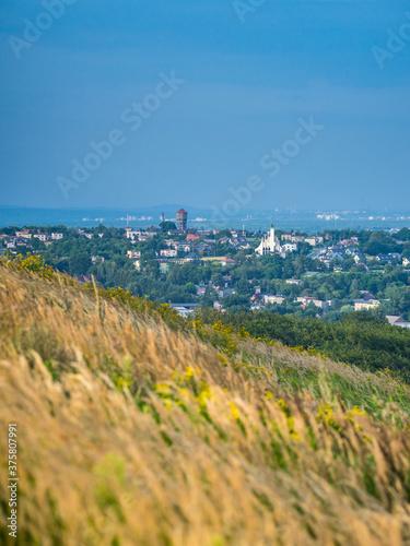 Papel de parede Sunny scenery of a grass hillside on Laziska Gorne's cityscape background in Pol