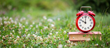 Save Time, Daylight Savings Concept, Alarm Clock On Old Books In The Grass, Web Banner With Copy Space