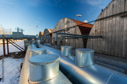 industrial concept - outdoor pipeline and old hangars in winter Fototapet