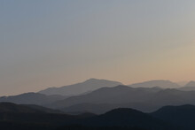 Weite Landschaft Mit Zum Horizont Hin Verschwimmenden Bergen Und Hügeln In Abendstimmung, Warme Farben