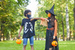canvas print picture - Two friends in Halloween costumes playing with each other in the park