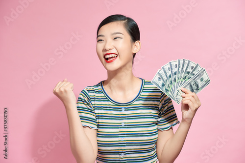 Photo Portrait of a cheerful young woman holding money banknotes and celebrating isola