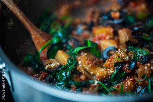 Fotografie, Obraz Guiso vegetariano close up berenjena espinacas hojas verdes jitomate cocido olla