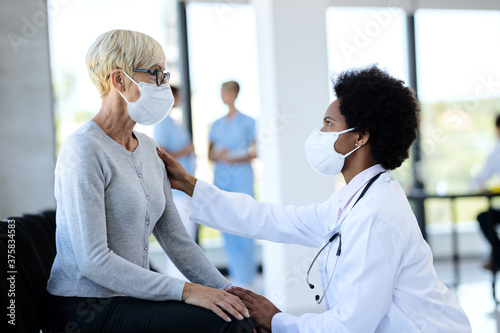 Tela Black doctor and mature patient wearing protective face masks while talking in waiting room at clinic
