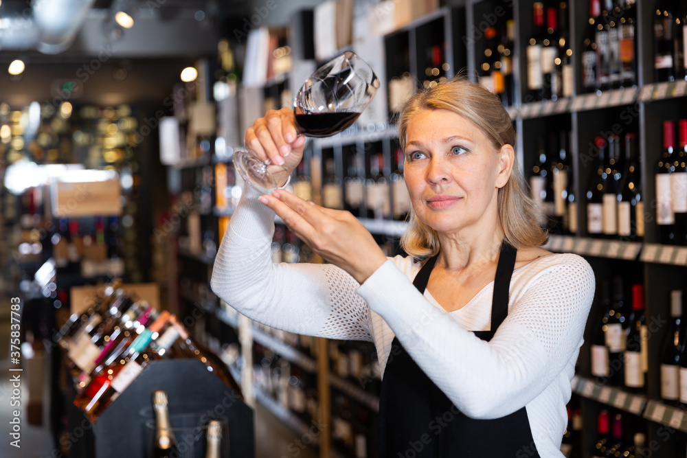 Fototapeta Portrait of middle aged woman professional sommelier tasting natural wines in winery ..