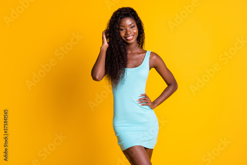 Photo portrait of african american girl touching hair with hand posing wearing blue dress isolated on bright yellow colored background