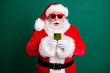 Photo Of Retired Stylish Grandpa White Beard Hold Telephone Open Mouth Shocked Unexpected Sale Wear Red Santa X-mas Costume Coat Gloves Sunglass Headwear Isolated Green Color Background