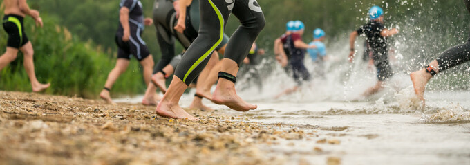 Legs of athletes in wetsuits running into a lake at a triathlon competition