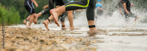 Fotografie, Obraz Athletes in wetsuits running into a lake at a triathlon competition