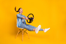 Full Length Profile Side Photo Of Astonished Positive Girl Taxi Rider Sit Chair Hold Steering Wheel Impressed Fast Speed Wear Style Stylish Clothes Isolated Bright Shine Color Background
