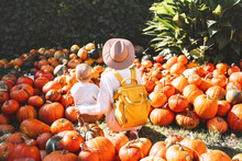 Mother And Child At Pumpkin Patch Outdoors.