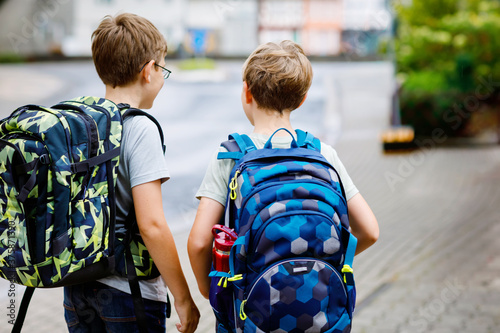 Photo Two little kid boys with backpack or satchel