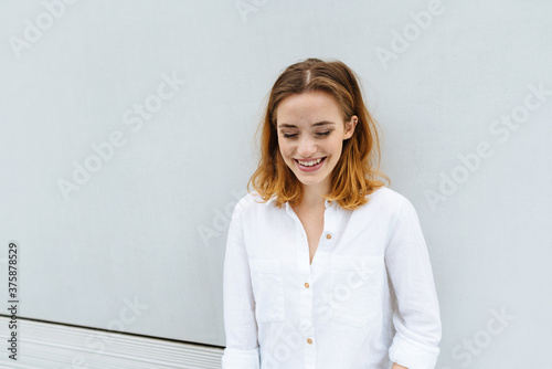 Young woman standing with downcast eyes Canvas Print