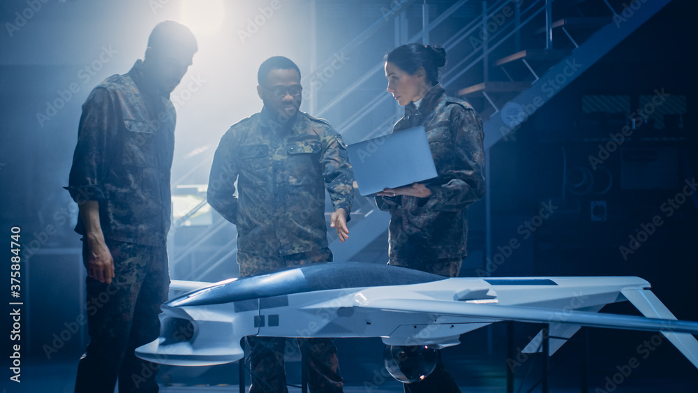 Fototapeta Army Aerospace Engineers Work On Unmanned Aerial Vehicle / Drone. Uniformed Aviation Experts Talk, Using Laptop. Industrial Facility with Aircraft for: Surveillance, Warfare Tactics, Air Strike