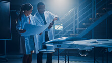 Two Aerospace Engineers Work On Unmanned Aerial Vehicle / Drone Prototype. Aviation Scientists In White Coats Holding Blueprints. Laboratory With Commercial Aerial Surveillance Aircraft