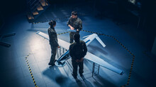 Army Aerospace Engineers Work On Unmanned Aerial Vehicle / Drone. Uniformed Aviation Experts Talk, Using Laptop. Industrial Facility With Surveillance, Warfare Tactics, Attack Machine. Elevated Shot