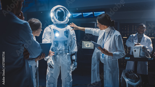 Obraz na płótnie Diverse Team of Aerospace Scientists and Engineers Wearing White Coats have Discussion, Use Computers Design New Space Suit Adapted for Galaxy Exploration and Travel