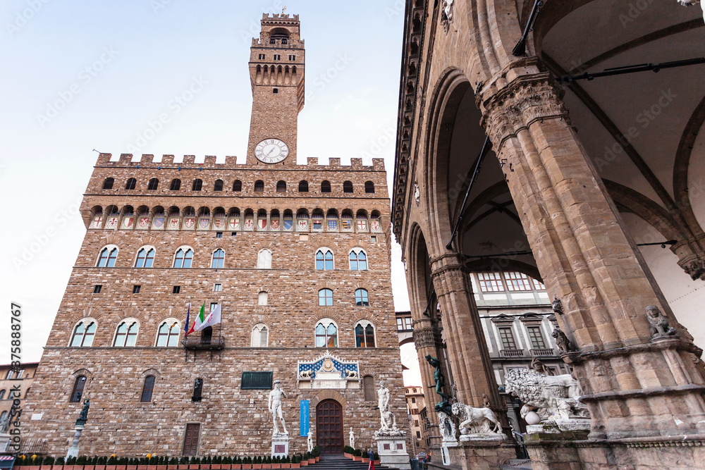 FLORENCE, ITALY - NOVEMBER 4, 2106: Facade of Palazzo Vecchio (Old Palace) with entrace in Museum and Loggia dei Lanzi in morning. The Palazzo Vecchio is the town hall of Florence city.