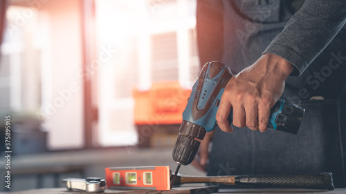 Fotografie, Obraz A man with a drill To repair the house
